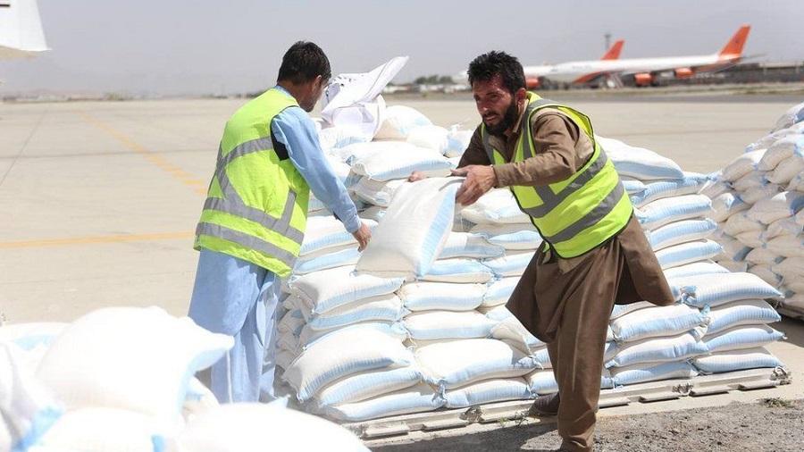 Doi muncitori afgani descarcă saci cu marfă
